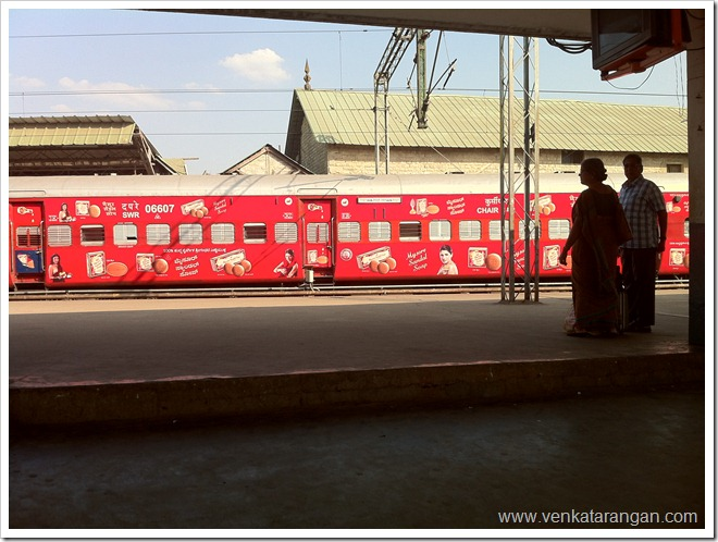 Bright red train coach in Bangalore city station