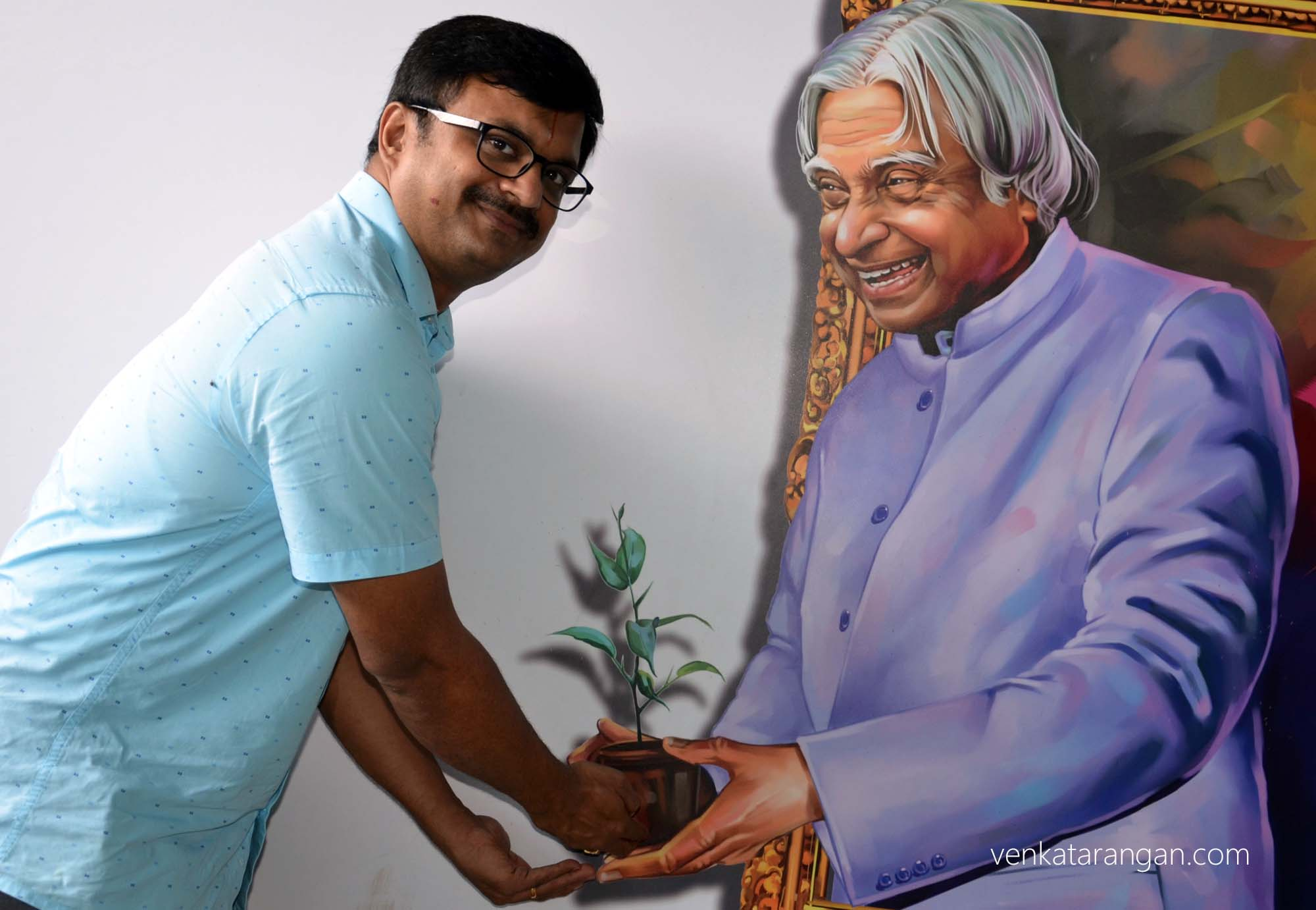In front of a 3-dimensional portrait of Dr A.P.J. Abdul Kalam