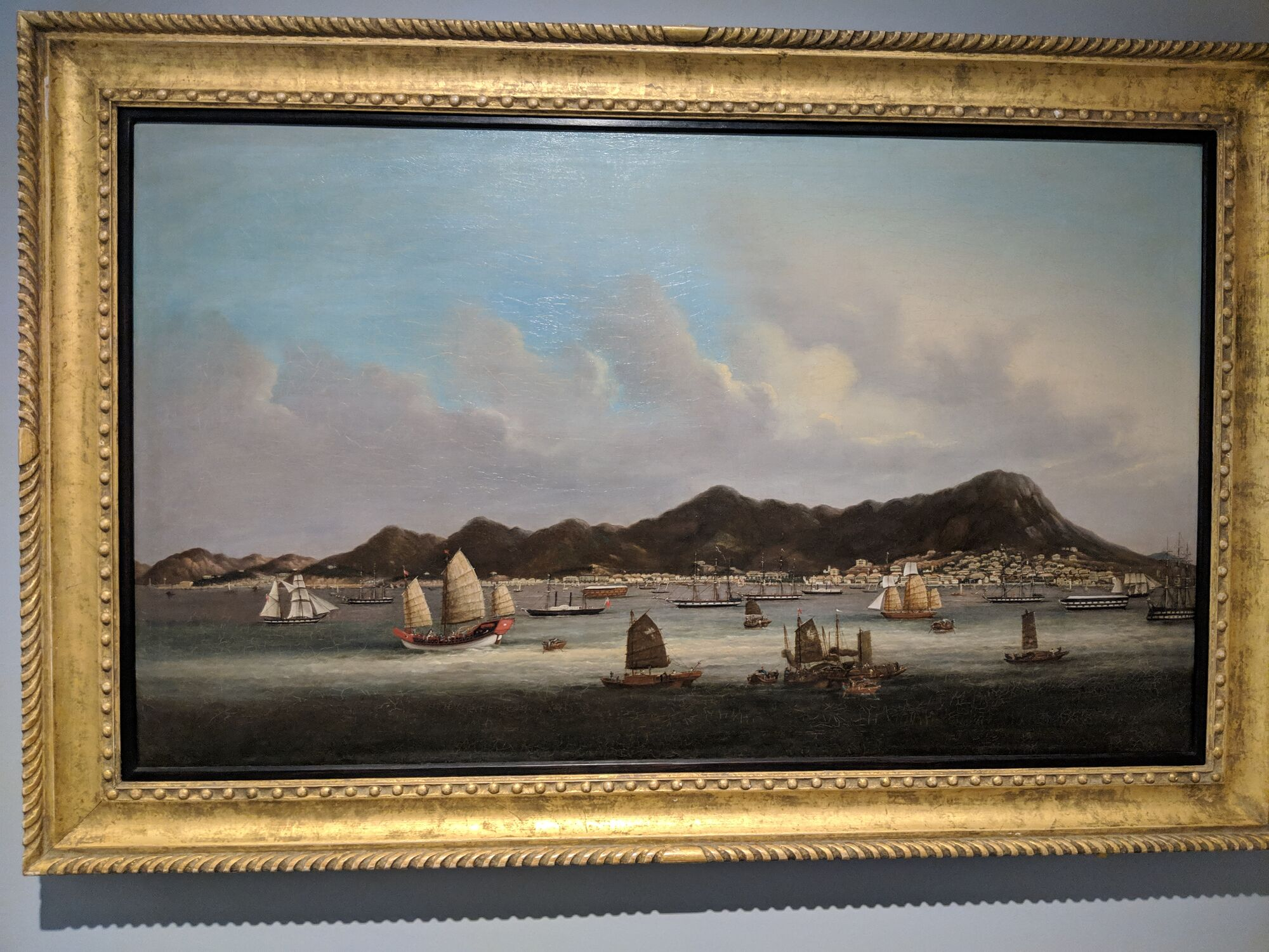 Hong Kong Island from the harbour, late 1850s, Oil on Canvas, includes several landmarks, such as St John's Cathedral (the white building with bell tower between the two mountains on the right) and Government House (1855) to the right and uphill.