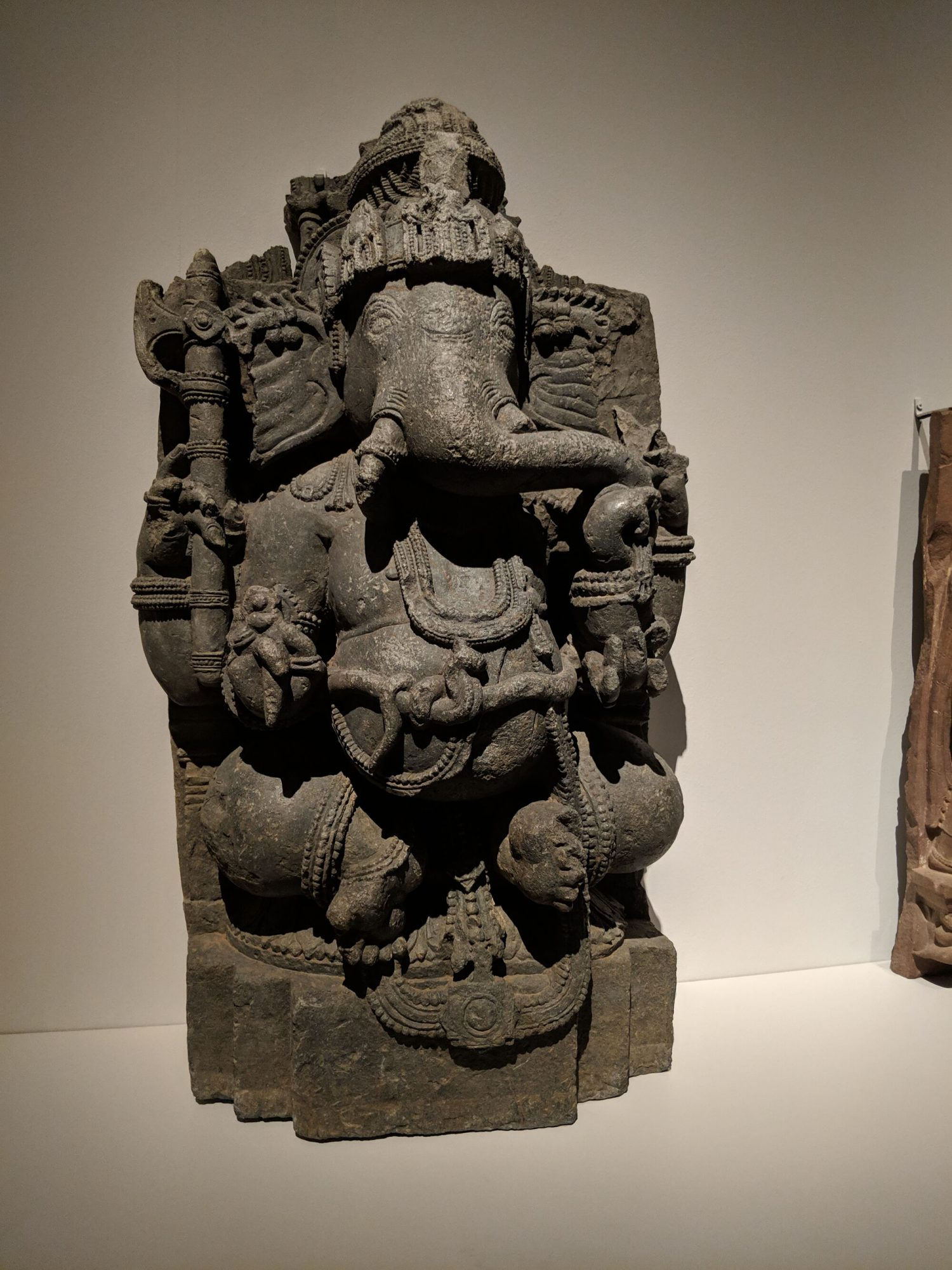 Ganesha, India, Karnataka, 12th century (Hoysala Empire). This four-armed Ganesha uses his trunk to tuck into a bowl of sweetmeats.