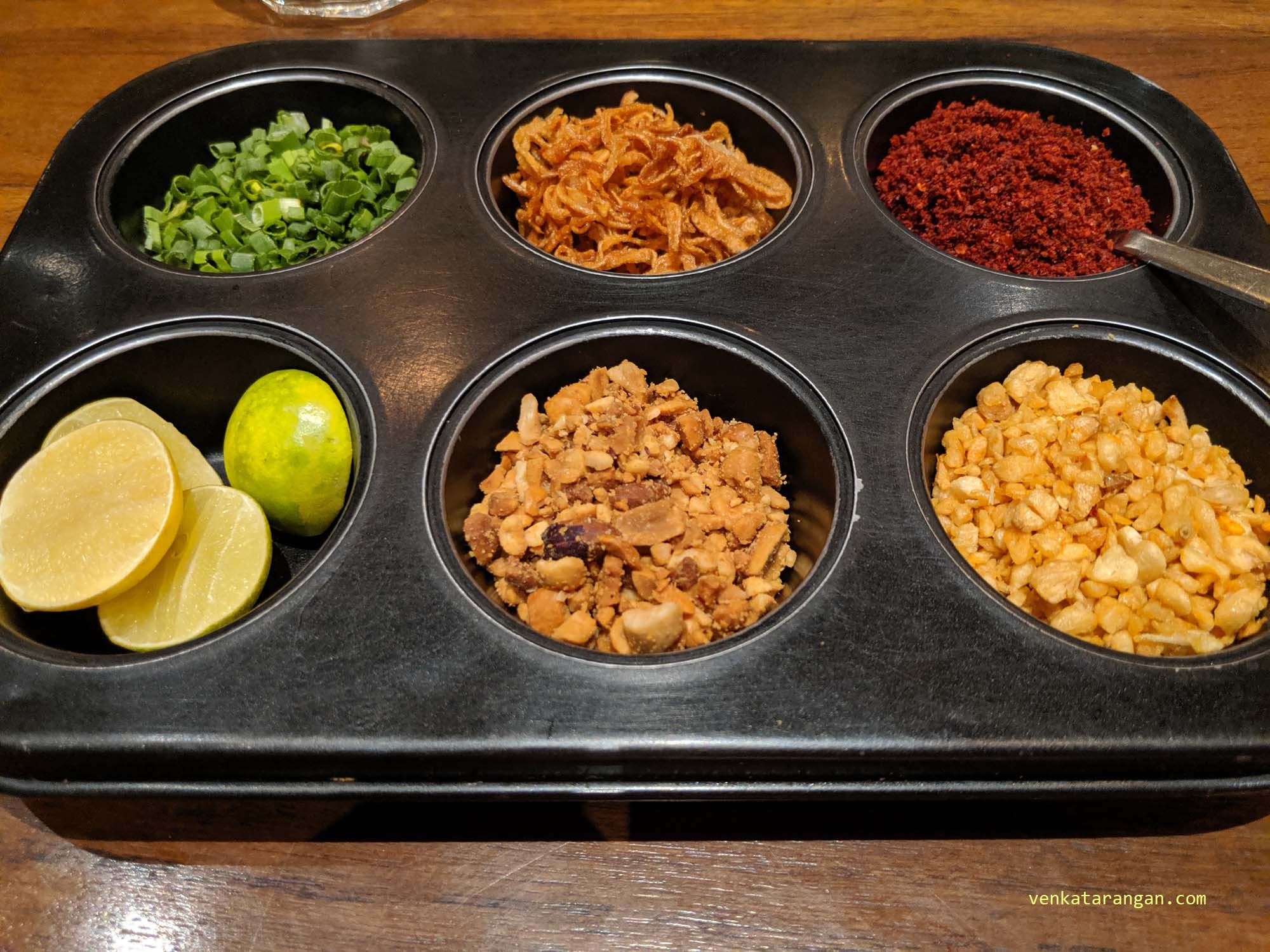Selection of condiments - cut lime, garlic savoury, red chili powder and roasted onions