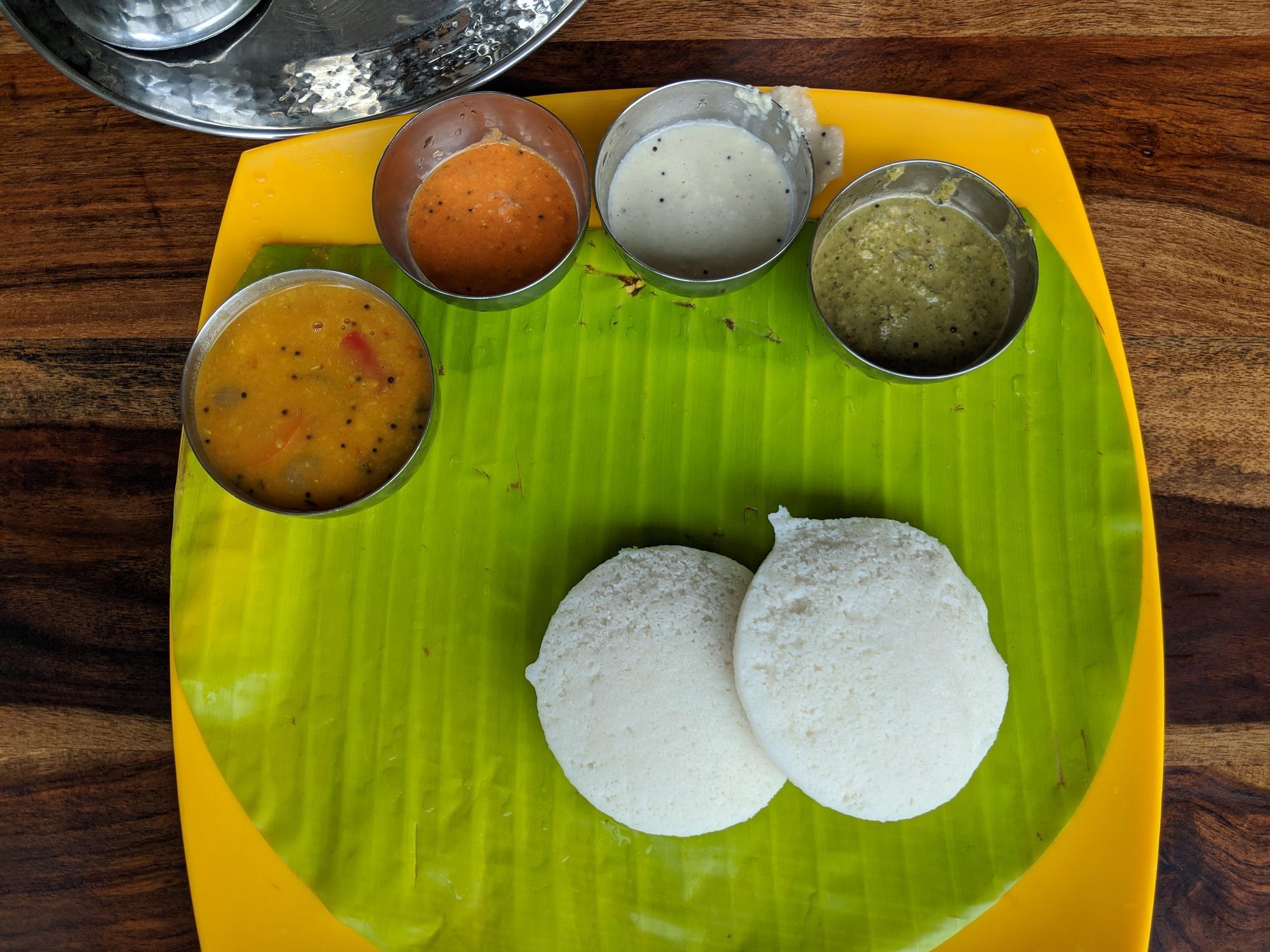 Idli (இட்லி) with Sambar, Tomato Chutney (தக்காளி சட்டினி), Coconut Chutney (தேங்காய் சட்டினி) and Coriander Chutney (கொத்தமல்லி சட்டினி).