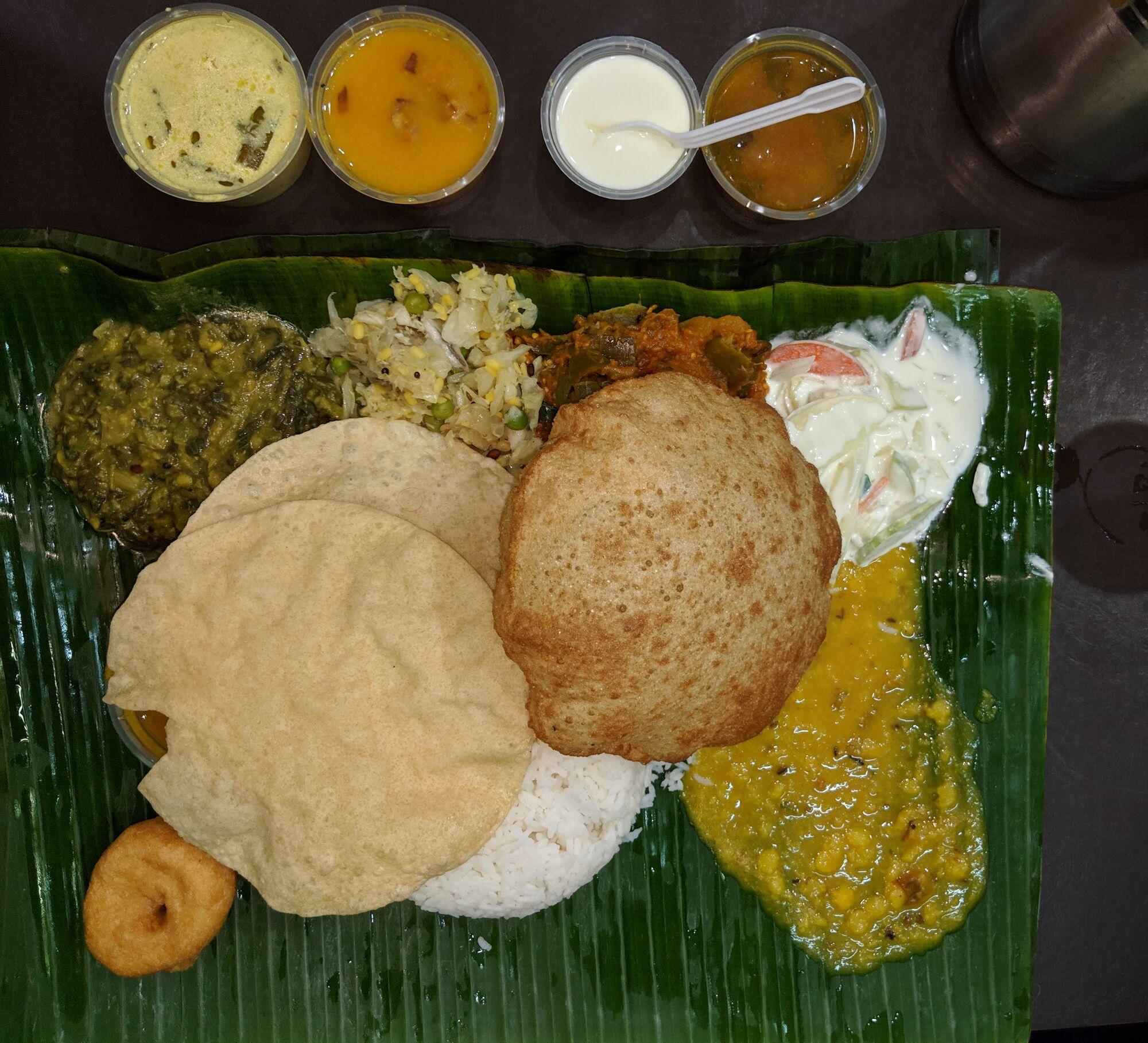 The famous meal of Komala Vilas with Rice, Poriyal, Curry, Sambar, Rasam, Curd, Poori, Vada, Raida and more.