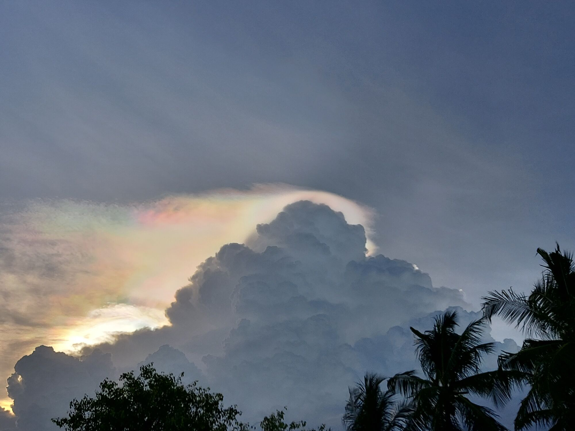 Clouds and a shy rainbow
